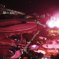 神宮外苑花火大会で打ち上がる花火。左は2020年東京五輪のメインスタジアムとなる新国立競技場=2019年8月10日、本社ヘリから