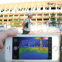 新国立競技場の前で準備体操するマラソン解説者の金哲彦さん(右)と川崎桂吾記者(左)。赤外線カメラで撮影すると木陰と日向での温度差がはっきりと見えた=東京都新宿区で2019年8月9日午前5時51分、宮武祐希撮影