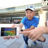 マラソンコースとなる日本橋で温度を測るマラソン解説者の金哲彦さん(中央)。赤外線カメラで道路を見ると真っ赤に染まっていた=東京都中央区で2019年8月9日午前6時54分、宮武祐希撮影