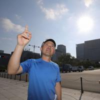 マラソンコースとなる皇居前で「日差しを遮るものが何もない難所です」と空を見上げるマラソン解説者の金哲彦さん(左)。右はマラソンコースを走る川崎桂吾記者=東京都千代田区で2019年8月9日午前7時37分、宮武祐希撮影