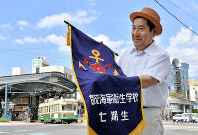 Mitsuyoshi Minoo holds the flag of his father's class at Kamo Kaigun Eisei Gakko, a school that produced nurses, doctors and other health professionals for the Imperial Japanese Navy, in front of Yokogawa Station in Hiroshima's Nishi Ward on Aug. 5, 2019. (Mainichi/Kenji Ikai)