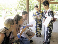 Students from Atomi University provide an explanation on heatstroke to foreigners visiting Hamarikyu Gardens in Tokyo's Chuo Ward, on Aug. 5, 2019. (Mainichi/Hitomi Tanimoto)