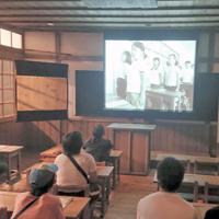 復元された国民学校の教室の黒板前に設置された映写幕に再現される戦時下の授業の様子。この後、空襲警報が鳴る