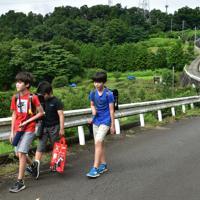 坂道を上り下りして登校するダニエルさん(右)とクリストファーさん(左)=秦野市で7月