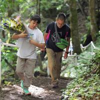 供花を手に御巣鷹山の尾根を登る人たち=群馬県上野村で2019年8月12日午前8時47分、滝川大貴撮影