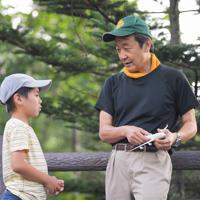 事故について飛行機の模型を使って説明を受ける子ども(左)=群馬県上野村で2019年8月12日午前6時38分、滝川大貴撮影