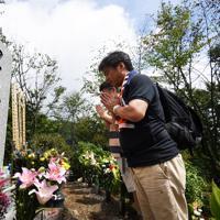 御巣鷹山の尾根にある「昇魂之碑」の前で手を合わせる人たち=群馬県上野村で2019年8月12日午前9時31分、滝川大貴撮影