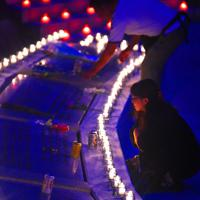 追悼慰霊式後、慰霊の園に刻まれた犠牲者の名前を見つめる遺族たち=群馬県上野村で2019年8月12日午後7時2分、滝川大貴撮影