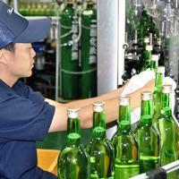 ヌーボーデラウェアの瓶を拭く社員=島根県出雲市大社町菱根の島根ワイナリーで、柴崎達矢撮影