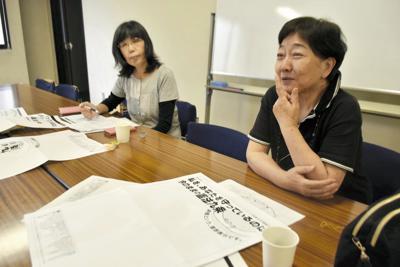 今年の意見広告のデザインを話し合う宮崎さん(右)