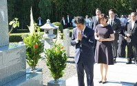 Prime Minister Shinzo Abe, foreground, puts his hands together in front of the grave of his father, former Foreign Minister Shintaro Abe, in Nagato, Yamaguchi Prefecture, on Aug. 13, 2019. His wife Akie is seen behind him. (Mainichi/Naoki Sugi)