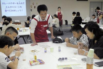 塗師さん(中央)に教わりながら、カレーパウダーを作る親子=毎日ホールで