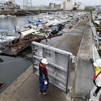 台風10号の接近に備えて、防潮扉を閉める作業員ら=広島市南区で2019年8月14日午後3時18分、木葉健二撮影