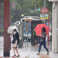 傘を差して足早に横断歩道を渡る人たち=宮崎市で2019年8月14日午後3時50分、津村豊和撮影