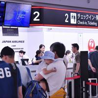 福岡空港の搭乗カウンターで手続きをする人たち=福岡市博多区で2019年8月15日午前9時15分、田鍋公也撮影