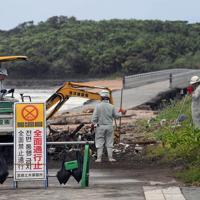 青島に続く橋のたもとにたまったごみを取り除く作業員=宮崎市で2019年8月15日午前8時59分、津村豊和撮影