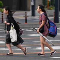 台風10号の強風で髪をなびかせながら歩く人たち=広島市南区で2019年8月15日午前8時7分、木葉健二撮影