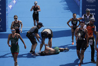 Mexico's Cecilia Perez, center, collapses after competing in a women's triathlon test event at Odaiba Marine Park, a venue for marathon swimming and triathlon at the Tokyo 2020 Olympics, on Aug. 15, 2019, in Tokyo. (AP Photo/Jae C. Hong)