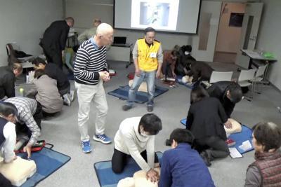 応急措置訓練をする朝倉勝美代表(黄色の上着の男性)ら「せき防災の会」のメンバー=同会提供