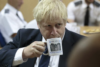 Britain's Prime Minister Boris Johnson takes a drink from a prison mug as he talks with staff during a visit to Leeds prison, Northern England, Tuesday Aug. 13, 2019. (AP Photo/Jon Super)