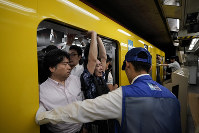 In this July 30, 2019 photo, a station attendant watches as a commuter struggles to squeeze himself into an overcrowded train during the morning rush hour at Akasaka Mitsuke Station in Tokyo. (AP Photo/Jae C. Hong)