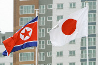 The North Korean and Japanese flags fly in the Incheon Asian Games athletes' village on Sept. 12, 2014. (Kyodo)
