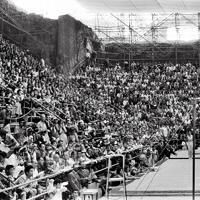 競技場を埋める観衆の中で、体操男子団体総合で鉄棒の演技する小野喬選手。小野選手は個人種目別の鉄棒と跳馬でもで金メダルを獲得した=カラカラ競技場で1960年(昭和35年)9月7日、二村次郎撮影(2枚の写真をつないでいます)