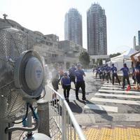 厳しい暑さの中、選手に水を手渡すスタッフ=東京都港区で2019年8月17日、佐々木順一撮影