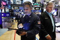 Traders John Romolo, left, and George Ettinger work on the floor of the New York Stock Exchange, on Aug. 16, 2019. (AP Photo/Richard Drew)