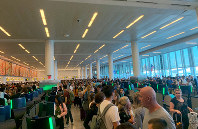 In this photo provided by Twitter user Brenna but in Leo Season, travelers stand in long lines to clear customs at John F. Kennedy International Airport, on Aug. 16, 2019, in New York, due to a temporary computer outage that affected U.S. Customs and Border Protection. (Brenna but in Leo Season via AP)