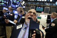 Trader Peter Tuchman works on the floor of the New York Stock Exchange, Friday, Aug. 16, 2019. (AP Photo/Richard Drew)