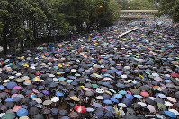 Protesters gather in Hong Kong on Sunday, Aug. 18, 2019. Thousands of people streamed into a park in central Hong Kong for what organizers hope will be a peaceful demonstration for democracy in the semi-autonomous Chinese territory. (AP Photo/Kin Cheung)