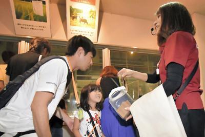 もろみを搾ってしょうゆにした後に残る「しょうゆかす」の香りをかぐ参加者たち=千葉県野田市で