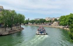 夏のセーヌ川を進む船はツアー客でいっぱい。右奥に人工ビーチ=筆者撮影