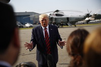 President Donald Trump speaks with reporters before boarding Air Force One at Morristown Municipal Airport in Morristown, N.J., on Aug. 18, 2019. (AP Photo/Patrick Semansky)
