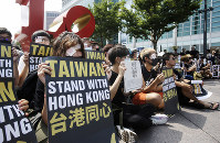 Hong Kong students living in Taiwan and Taiwanese supporters with their eyes covered in eyepatches, symbolizing a woman reported to have had an eye ruptured by a beanbag round fired by police during clashes, hold slogans during a rally in Taipei, Taiwan, Saturday, Aug. 17, 2019. (AP Photo/Chiang Ying-ying)