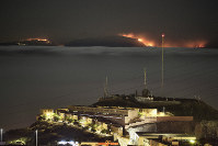 The fire on the mountains of the Canary Islands is pictured from Santa Cruz de Tenerife island, Spain, early on Aug. 19, 2019. (AP Photo/Andres Gutierrez)