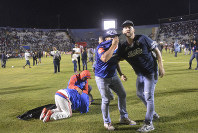 Soccer fans gather on the field in an attempt to escape tear gas that was fired by police who were trying to break up a deadly fight between fans before the start of a game between Motagua and Olimpia, at the national stadium in Tegucigalpa, Honduras, late on Aug. 17, 2019. (Victor Colindres/La Tribunal via AP)