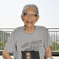 自身の戦争経験をまとめた著書「悔恨の足跡」を手にする増田俊美さん(102)=甲府市で