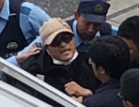 Fumio Miyazaki, the suspect in a widely publicized road-rage incident on the Joban Expressway, is seen detained by police investigators in the western Japan city of Osaka on Aug. 18, 2019. (Photo taken from a video image provided by a nearby resident)