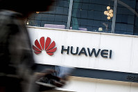 In this July 30, 2019, file photo a woman walks by a Huawei retail store in Beijing. The U.S. government gave chipmakers and technology companies a 90-day extension to sell products to technology giant Huawei. (AP Photo/Andy Wong)
