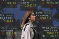 A woman walks by an electronic stock board of a securities firm in Tokyo, on Aug. 20, 2019. (AP Photo/Koji Sasahara)