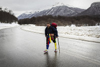 Venezuelan Yeslie Aranda, 57, walks on Route 3 between Tolhuin and Ushuaia, Argentina, on Aug. 17, 2019. Aranda left his hometown of San Cristobal in the southeastern state of Tachira last year with a backpack, $30 in his pocket and an aluminum prosthesis that enabled him to negotiate the continent's rugged roads. (AP Photo/Lujan Agusti)