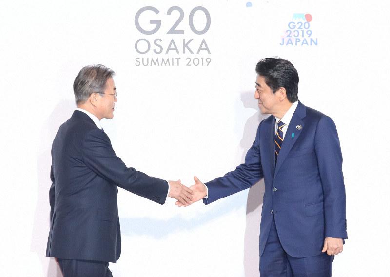 韓国の文在寅大統領(左)を出迎える安倍晋三首相=2019年6月28日、代表撮影