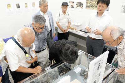 資料について説明する慶応大福澤研究センター准教授の都倉武之さん(右から2人目)=大阪市北区で