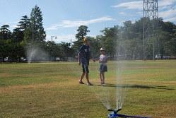 近くの最高気温が40度を超えた日に、芝生のスプリンクラーの水を浴びる子どもたち=新潟県上越市の高田公園芝生広場で2019年8月14日