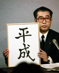 In this file photo taken on Jan. 7, 1989, then Chief Cabinet Secretary Keizo Obuchi shows off a sign reading