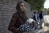 Ulfat, a Kashmiri woman holds her forty days old daughter Tanzeela, as she waits outside a police station to hear about her husband who was detained during night raids in Srinagar, Indian controlled Kashmir, on Aug. 20, 2019. (AP Photo/ Dar Yasin)