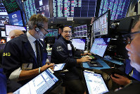 Specialist Anthony Matesic, center, works with traders at his post on the floor of the New York Stock Exchange, on Aug. 21, 2019. (AP Photo/Richard Drew)