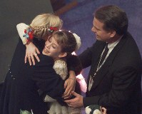 In this Feb. 15, 1997 file photo, figure skater Tara Lipinski with her coach Richard Callaghan receives a hug after it was announced she won the gold medal at the U.S. Figure Skating Championships in Nashville, Tenn. (AP Photo/Cliff Schiappa)